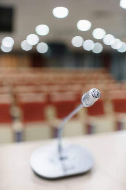 microfono in primo piano. presentazione del seminario. sala conferenze piena di posti vuoti. colore rosso. sala per workshop e seminari - theatre full of people stage foto e immagini stock