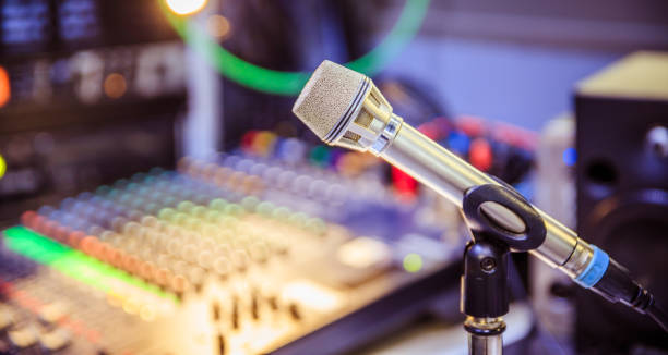 Microphone in the recording studio, equipment in the blurry background stock photo