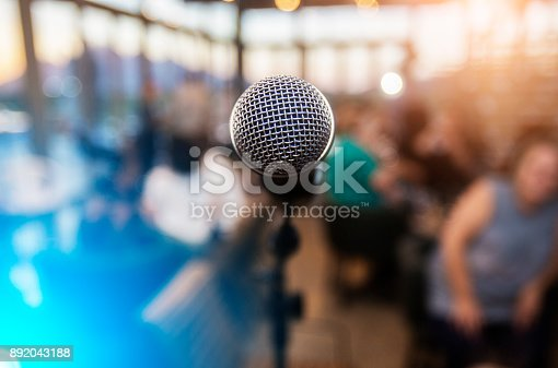 istock Microphone infront of an out of focus audience 892043188