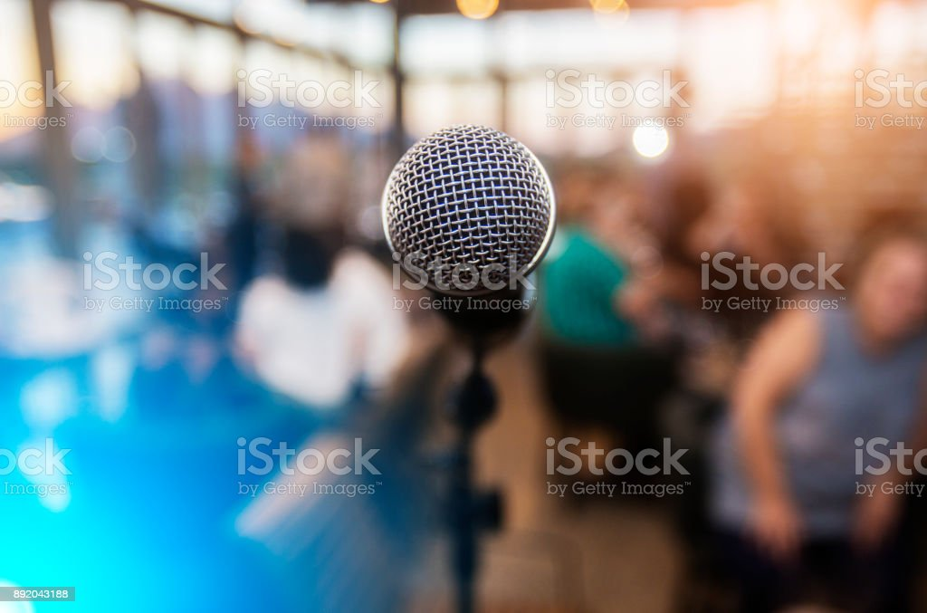 Microphone infront of an out of focus audience stock photo