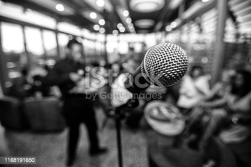 671733994 istock photo Microphone infront of defocused audience 1168191650