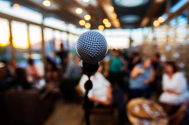 Microphone infront of out of focus  people waiting stock photo