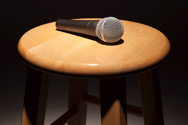 Microphone Laying on Wooden Stool Under Spotlight Microphone Laying on Wooden Stool Under Spotlight Abstract. stool stock pictures, royalty-free photos & images