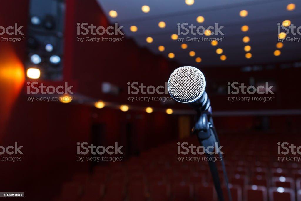 Mikrofon auf einem Hintergrund von dunklen Halle mit Sitzplätzen für die Zuschauer – Foto