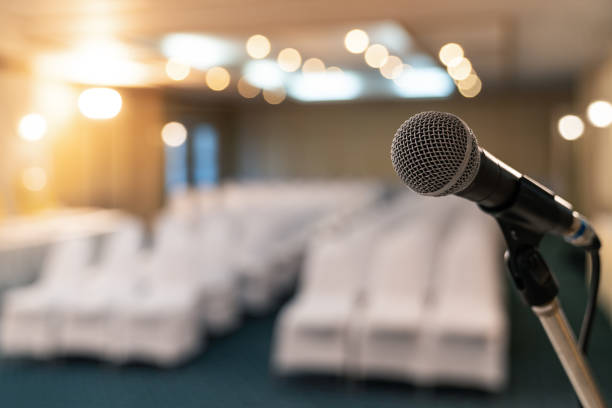 Microphone on abstract blurred of speech in seminar room or speaking conference hall light, Event Background stock photo