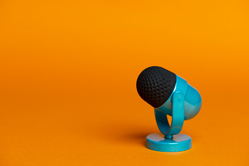 Blue microphone on orange colored background.