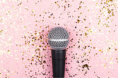 istock A microphone on pink background decorated with confetti. Minimal compostion. 1257944704