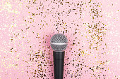 istock A microphone on pink background decorated with confetti. Minimal compostion. 1270615498
