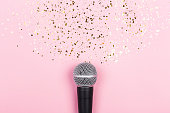 istock A microphone on pink background decorated with confetti. Minimal compostion. 1271926605
