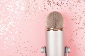 istock A microphone on pink background decorated with confetti. Minimal compostion. 1280360339