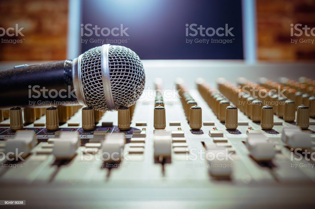 microphone on sound mixer with computer monitor background stock photo