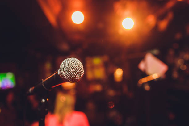 Microphone on stage against a background of auditorium. Microphone on stage against a background of auditorium performance stock pictures, royalty-free photos & images