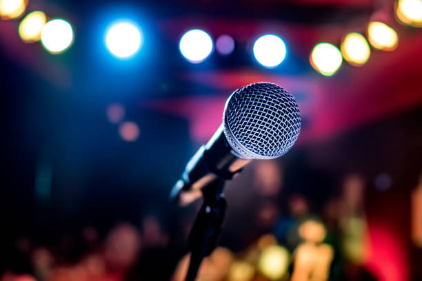 Microphone on stage against a background of auditorium. Public performance on stage Microphone on stage against a background of auditorium. Shallow depth of field. Public performance on stage. microphone stock pictures, royalty-free photos & images