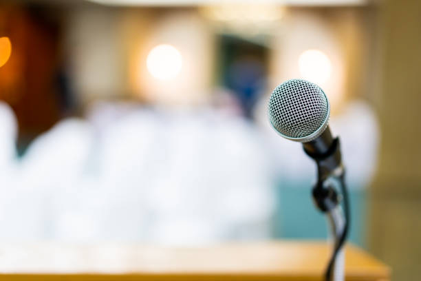 Microphone on stage close up. Wired microphone set up on the front of conference room close up with blurred background.  Wired microphone close up with copy space background. publicity event stock pictures, royalty-free photos & images