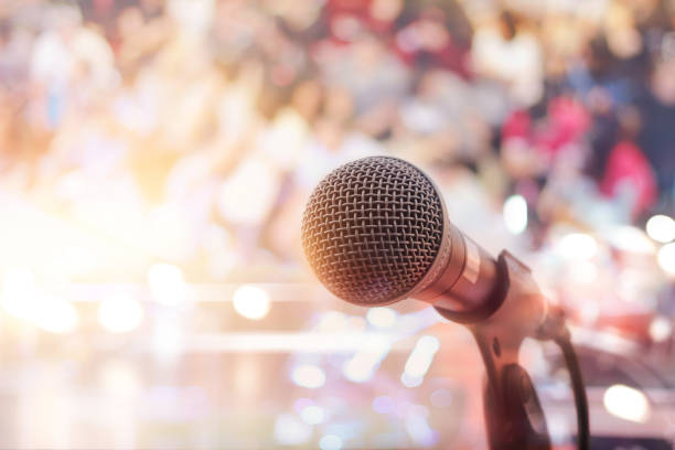 Microphone on stage in concert with people background Microphone on stage in concert with people background singer stock pictures, royalty-free photos & images