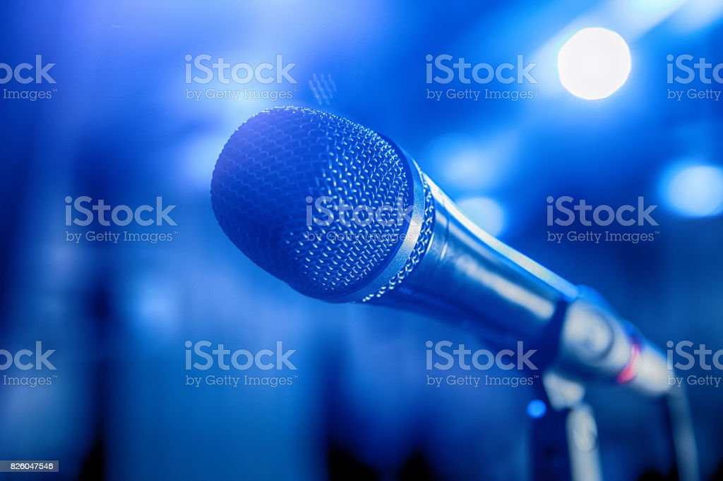 microphone on stage with blue background stock photo