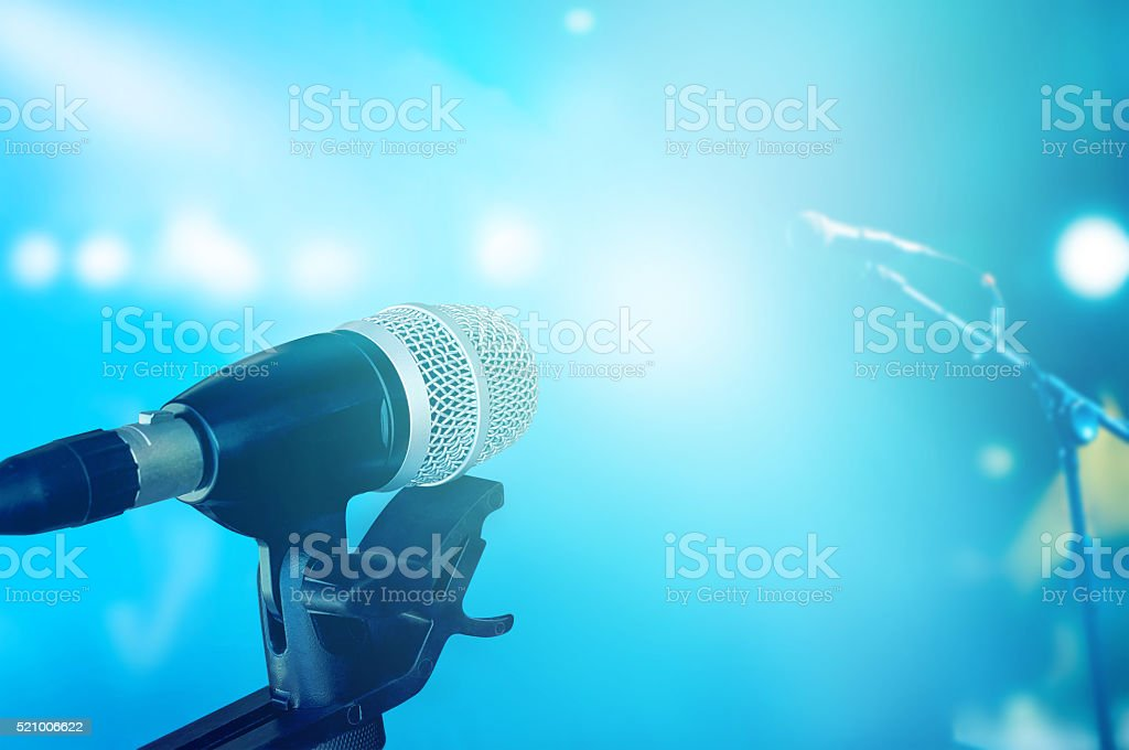 Microphone on stage with blue vibrant lighting concert stock photo