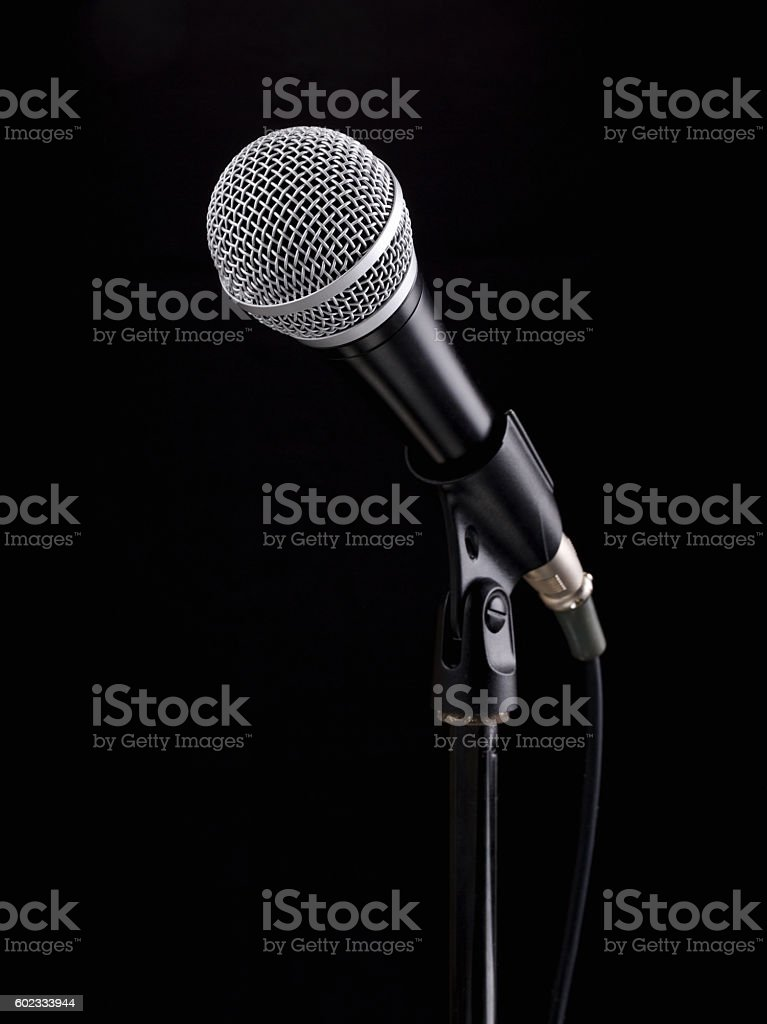 Microphone on stand against a black background stock photo