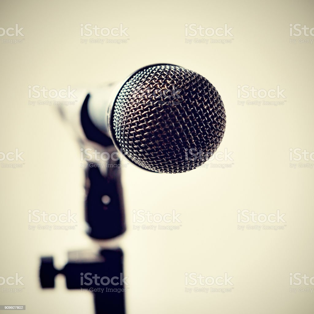 Microphone on stand against pale background stock photo