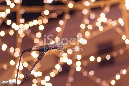 Microphone on stand with smooth soft warm light bokeh background in orange yellow and pink. Concept for live performance, stage, artist, musician, singer, happy times, fun, joy.