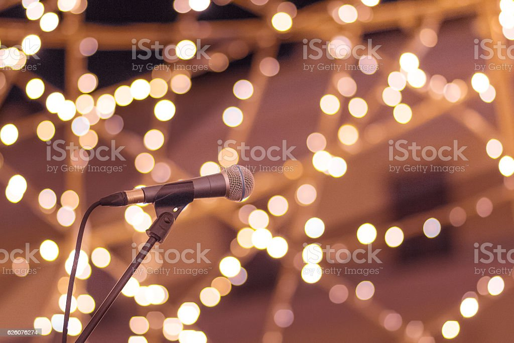 Microphone on stand with smooth soft warm light bokeh background stock photo