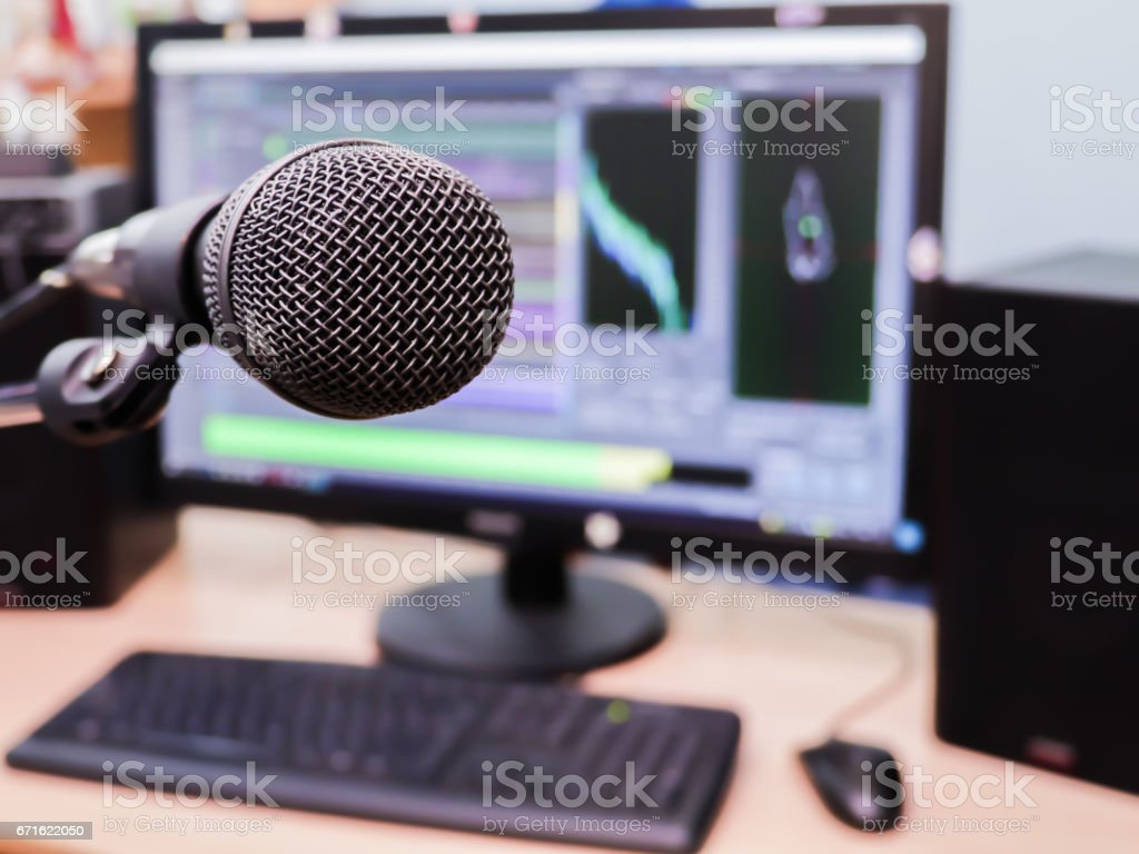 Microphone on the background of the computer monitor. Home recording Studio. Close-up. The focus in the foreground. Blurred background. Software for recording and editing sounds stock photo