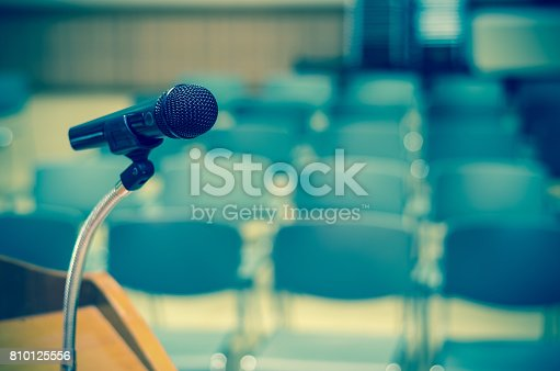 istock Microphone on the speech podium over the Abstract blurred photo of conference hall or seminar room background 810125556