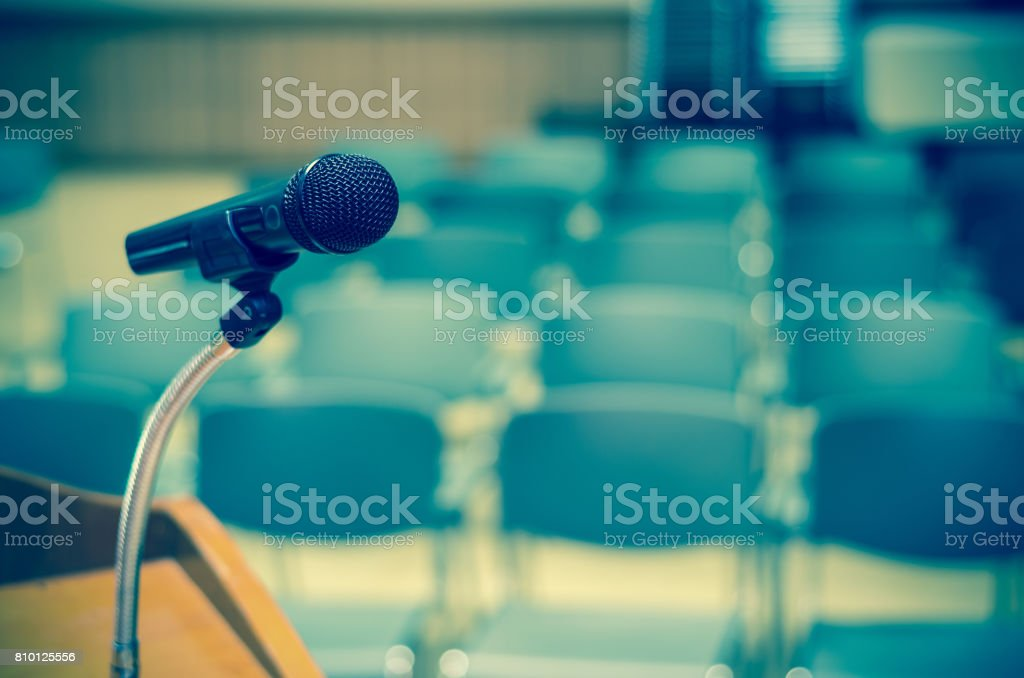 Microphone on the speech podium over the Abstract blurred photo of conference hall or seminar room background stock photo