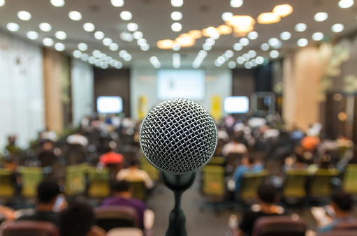 istock Microphone over the Abstract blurred photo of conference hall or 615072736