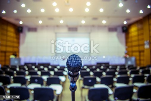 istock Microphone over the Abstract blurred photo of conference hall or seminar room background 820814078