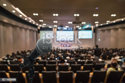istock Microphone over the Abstract blurred photo of conference hall or seminar room with attendee background, Business meeting concept 821463698