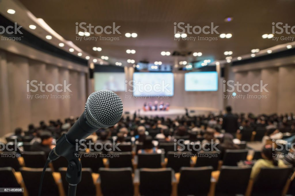 Microphone over the Abstract blurred photo of conference hall or seminar room with attendee background, Business meeting concept stock photo