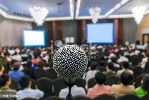821463698istockphoto Microphone over the Abstract blurred photo of conference hall or seminar room with attendee background, Business meeting concept 825186894