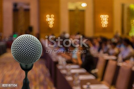 821463698istockphoto Microphone over the Abstract blurred photo of conference hall or seminar room with attendee background 825187104