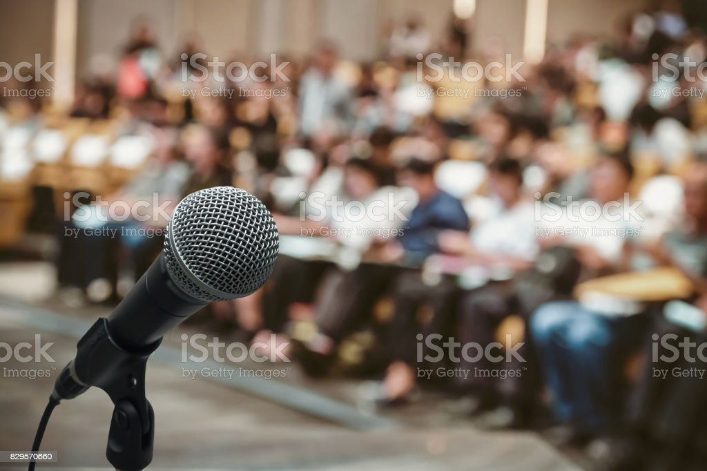 Microphone over the Abstract blurred photo of conference hall or seminar room with attendee background stock photo