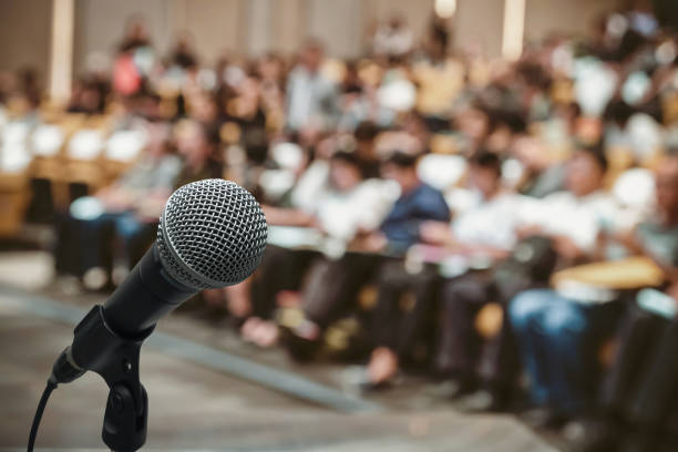 microphone over the abstract blurred photo of conference hall or seminar room with attendee background - meeting imagens e fotografias de stock