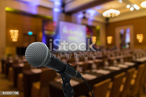 821463698istockphoto Microphone over the Abstract blurred photo of conference hall or seminar room with attendee background 843301796