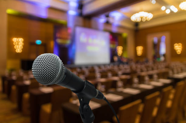 microphone over the abstract blurred photo of conference hall or seminar room with attendee background - press conference stock photos and pictures
