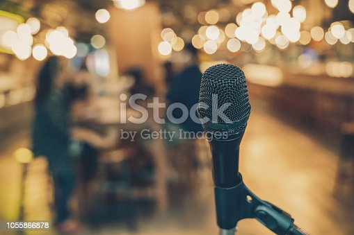 istock Microphone over the Abstract blurred photo of people group having the meeting in public working space or seminar room, misucal and education with modern lifestyle concept 1055866878