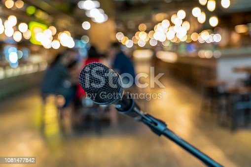 istock Microphone over the Abstract blurred photo of people group having the meeting in public working space or seminar room, misucal and education with modern lifestyle concept 1081477842