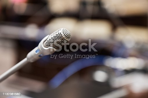 istock Microphone over the blurred business forum Meeting or Conference Training Learning Coaching Room Concept, Blurred background. 1132381582
