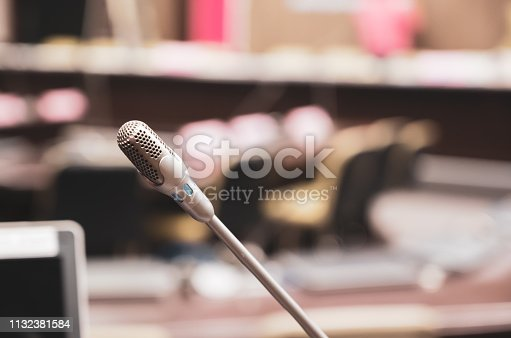 1132381614istockphoto Microphone over the blurred business forum Meeting or Conference Training Learning Coaching Room Concept, Blurred background. 1132381584