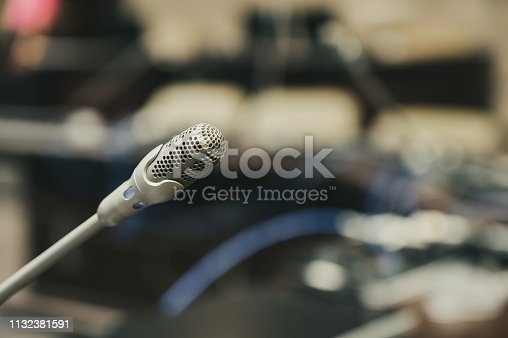 1132381614istockphoto Microphone over the blurred business forum Meeting or Conference Training Learning Coaching Room Concept, Blurred background. 1132381591