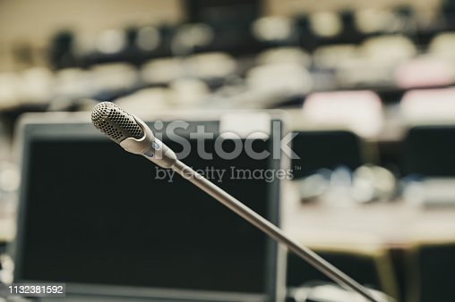 1132381614istockphoto Microphone over the blurred business forum Meeting or Conference Training Learning Coaching Room Concept, Blurred background. 1132381592