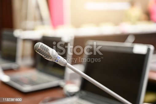 1132381614istockphoto Microphone over the blurred business forum Meeting or Conference Training Learning Coaching Room Concept, Blurred background. 1132381600