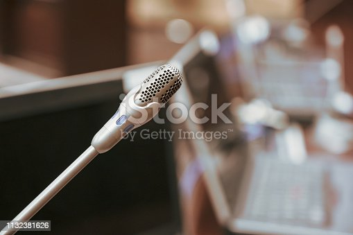 1132381614istockphoto Microphone over the blurred business forum Meeting or Conference Training Learning Coaching Room Concept, Blurred background. 1132381626