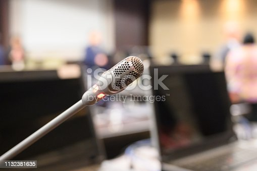 1132381614istockphoto Microphone over the blurred business forum Meeting or Conference Training Learning Coaching Room Concept, Blurred background. 1132381635