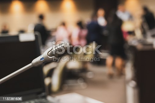 1132381614istockphoto Microphone over the blurred business forum Meeting or Conference Training Learning Coaching Room Concept, Blurred background. 1132381636
