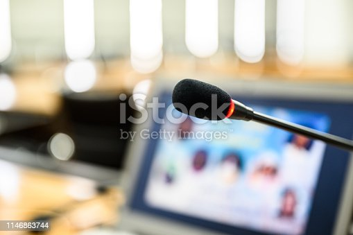 814301186istockphoto Microphone over the blurred business forum Meeting or Conference Training Learning Coaching Room Concept, Blurred background. 1146863744