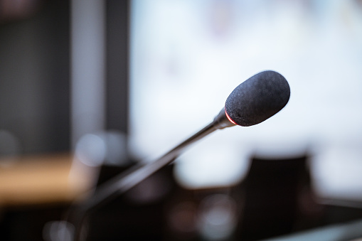 831720990 istock photo Microphone over the blurred business forum Meeting or Conference Training Learning Coaching Room Concept, Blurred background. 1146863788